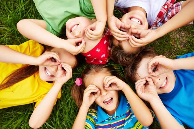 5 børn der ligger og fjoller på græsset