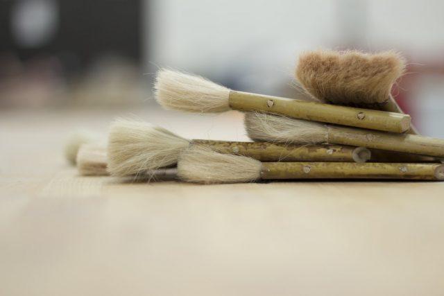 Forskellige malerpensler der ligger på et trægulv