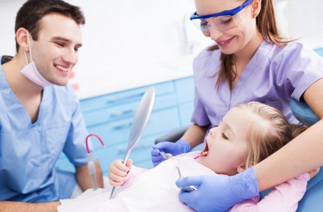 En tandlæge og tandplejer kigger på en piges tænder